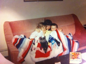 A picture of my brother, sister, cat and I when we were all kids. I'm in the middle.